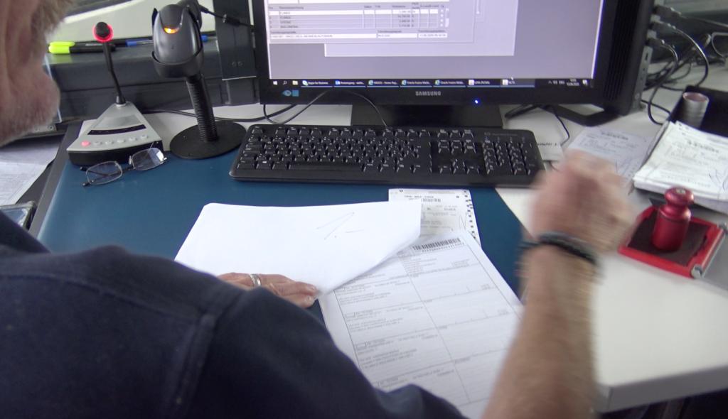 Person stempelt dokumente an einem Arbeitsplatz, im hintergrund der Bildrschirm und Tastatur.