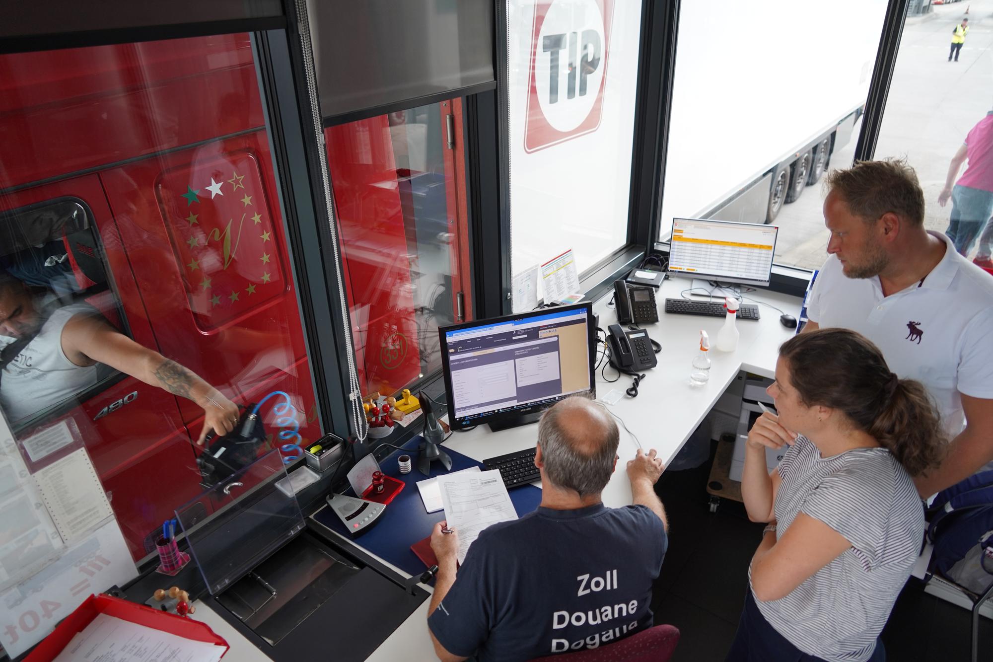Ein Zollmitarbeiter fertigt in der Hochkabine der Zollstelle einen LKW ab, zwei Personen beobachten ihn dabei.