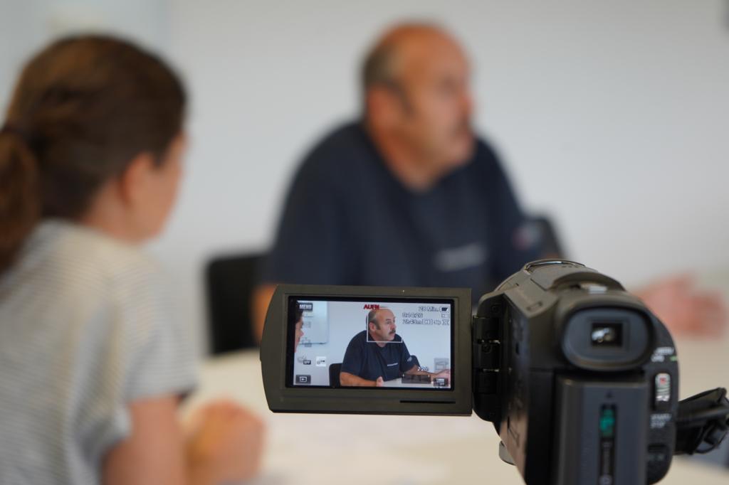 Im Vordergrund Videokamera mit Fokus auf den Interviewpartner, Interviewsituation verschwommen im Hintergrund.